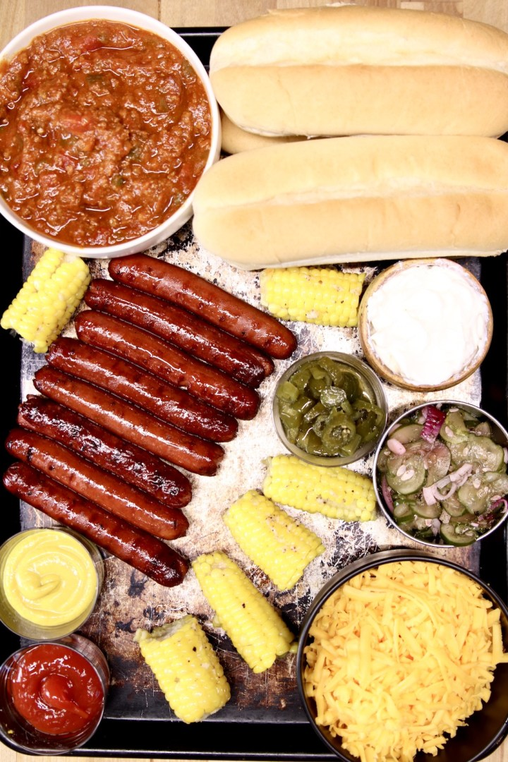 tray of grilled hot dogs, chili, buns, cheese, condiments for chili cheese dogs