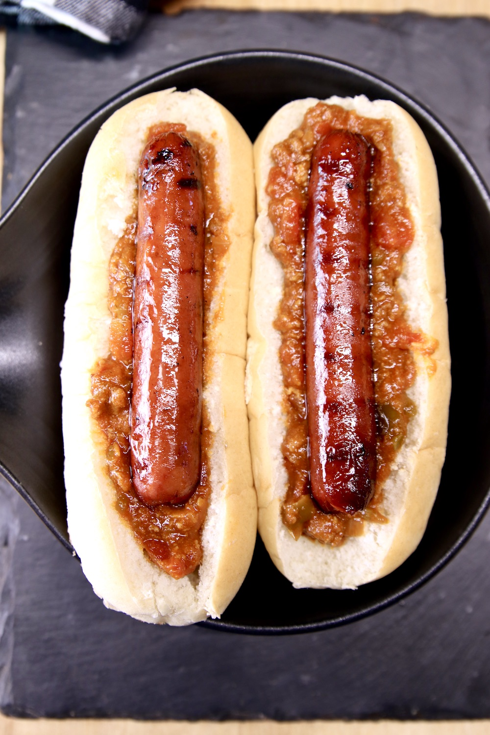 2 hoagie buns with chili and hot dogs