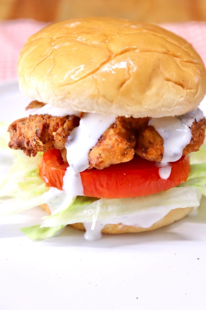 Crispy chicken sandwich with lettuce, tomato and ranch dressing - close up