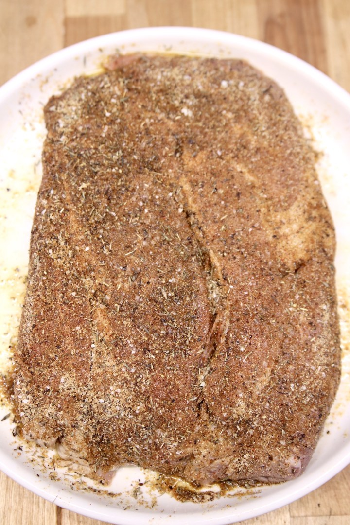 chuck roast coated with dry rub ready to grill