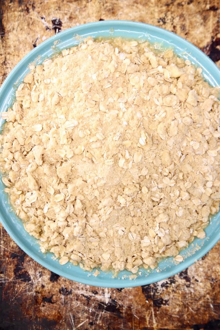 pineapple crisp in a pie plate on a baking sheet