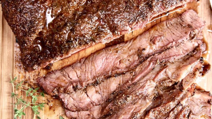 grilled chuck roast on a board, partially sliced
