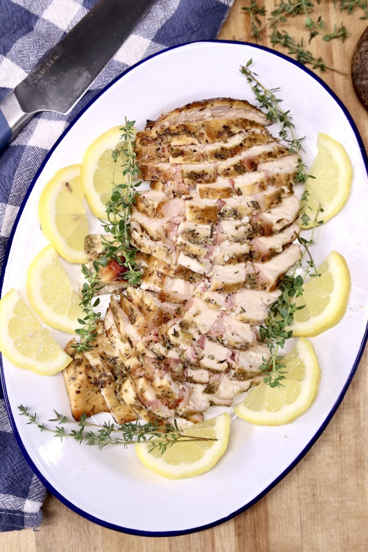 platter of sliced chicken breast with lemon and thyme garnish
