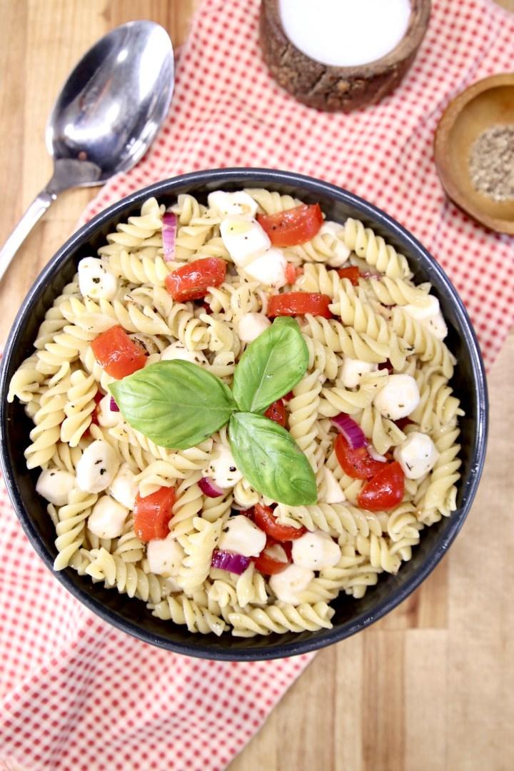 Pasta Salad with tomatoes, mozzarella, basil garnish in a black bowl