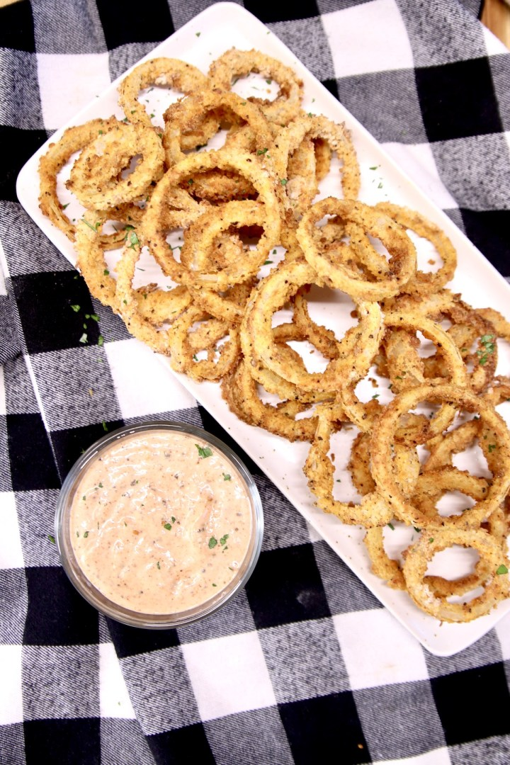 onion rings on a platter with dipping sauce