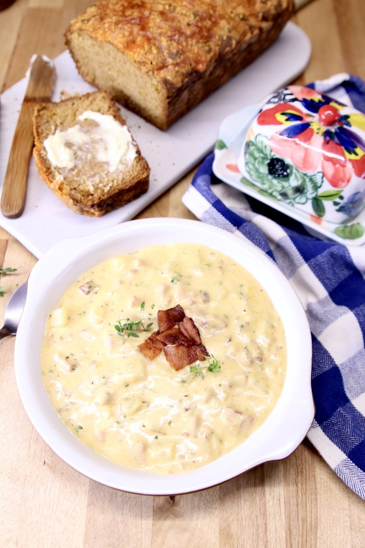 bowl of creamy soup with loaf of beer bread