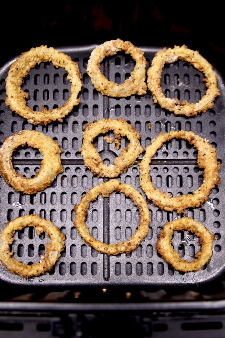 air fryer basket with golden brown onion rings