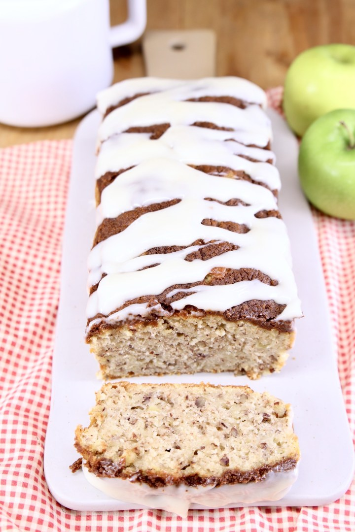 Apple bread with cream cheese drizzle on a board - one slice in front of loaf, apples in back ground