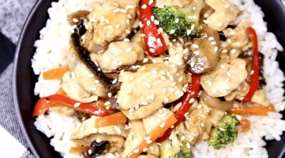 chicken stir fry over rice in a black bowl