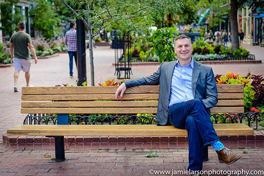 Steve Cuss smiling and  sitting calmly on a park bench with his legs crossed and one arm resting on the top of the bench. Steve is the author of Managing Leadership Anxiety: Yours and Theirs