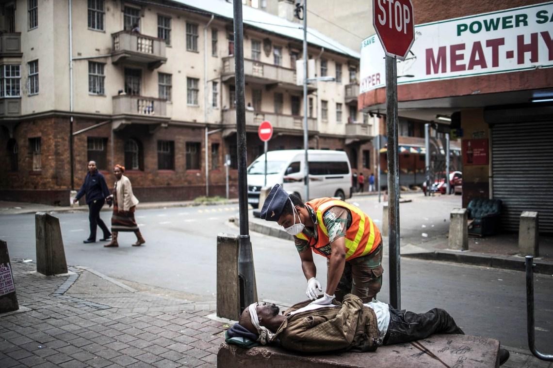 Johannesburg. Durante un pattugliamento nelle strade di Hillbrow un poliziotto della difesa nazionale (SANDF) controlla un senzatetto stremato da una overdose