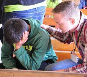 Tim praying for one of the kids at the summer camp