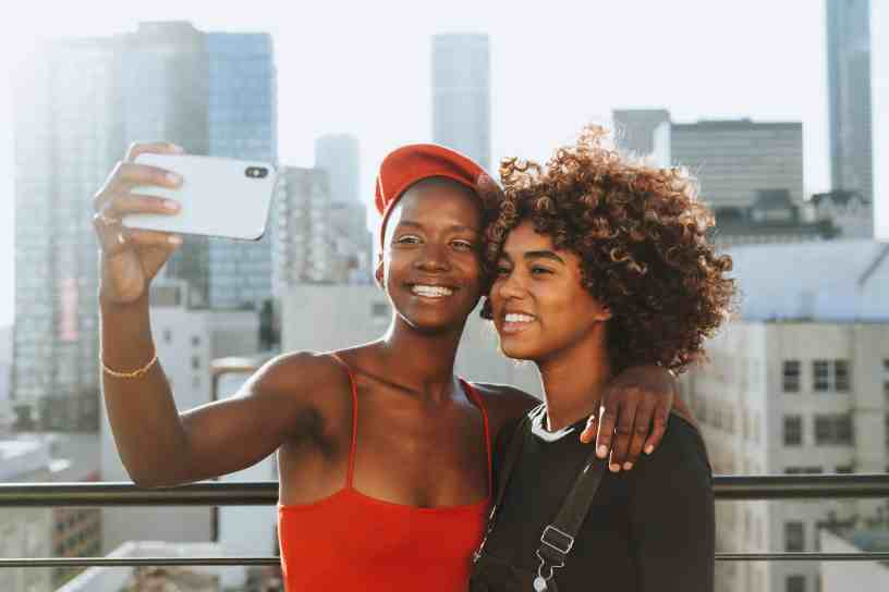 Two African-American teenagers taking a selfie on top of a large building