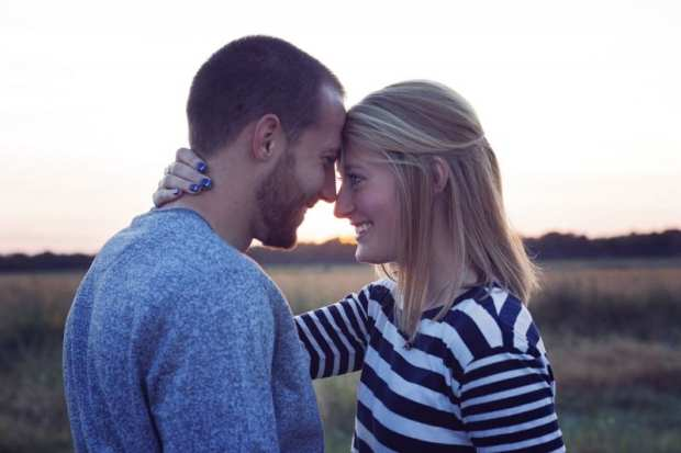girl and boy with foreheads pressed together talking about wedding prep