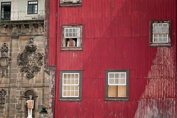 man looking out of window of red building thinking about how to travel when you're young