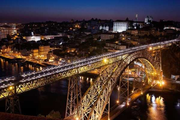 nighttime photo of bridge in Portugal showing why you should travel when you're young