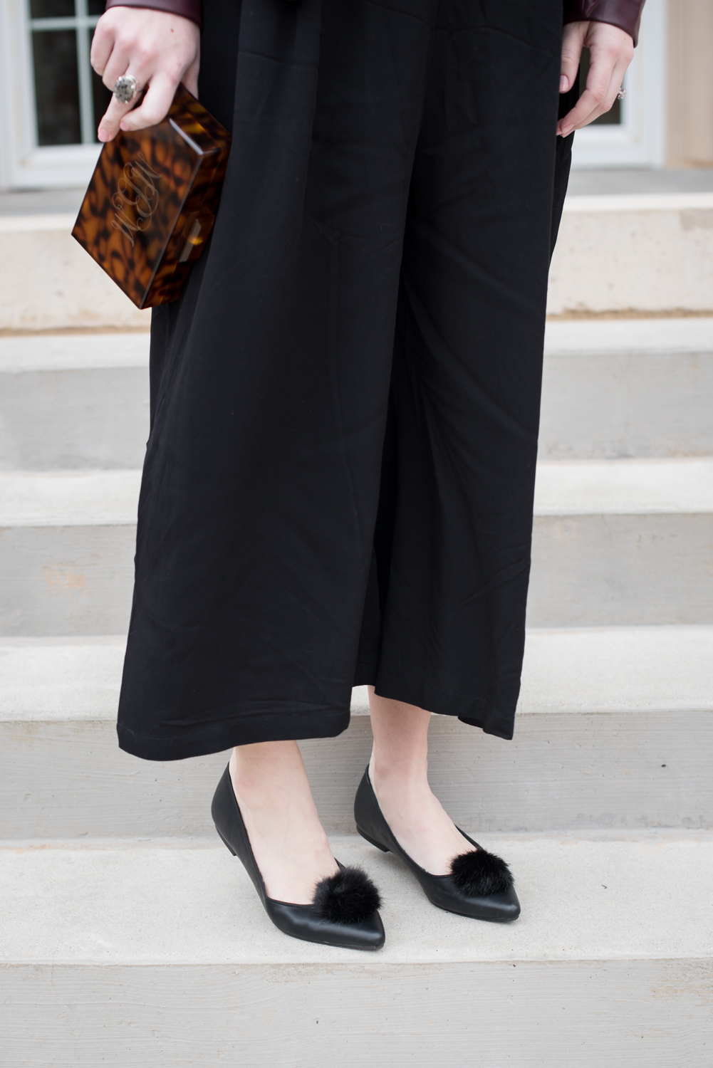 How to wear a wide leg jumpsuit in the winter featured by top US fashion blogger, Miss Molly Moon: image of a woman wearing a BB Dakota faux leather jacket, Marley Lilly clutch, Mary Jane Ballet flats