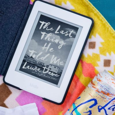 summer reading. close up image of a kindle and sparkling water can lying on a bright-colored beach towel