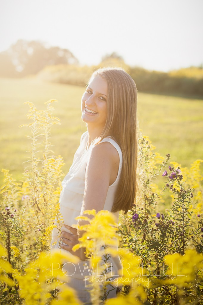 senior girl standing in a field pittsburgh backlit