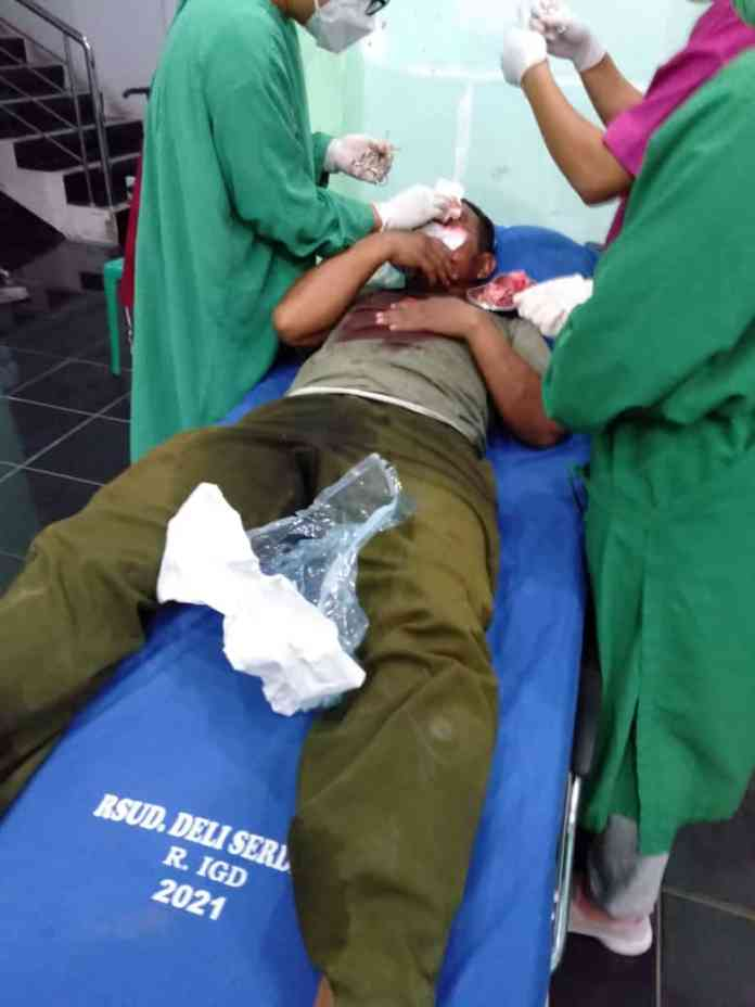 Serda Mulyaman saat diobati luka di jidatnya oleh petugas RSUD Deli Serdang. (f:mistar/ist)