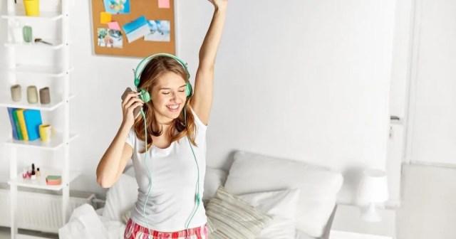Girl dancing with earphones in living room
