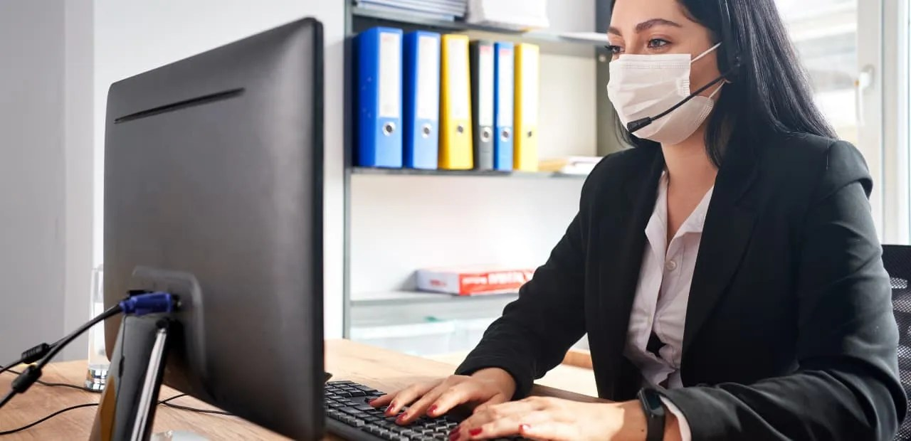 return to the office- Female employee with face mask.