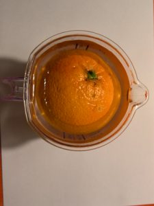 Eine Apfelsine mit Schale schwimmt in Wasser.