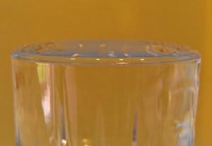 Gewölbte Wasseroberfläche in einem Glas.