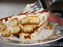 tiramisu cake on a plate with a fork next to it