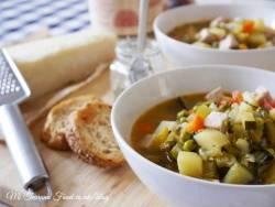 vegetable soup in a white bowl with bread slices on the side