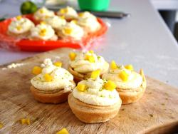 4 tarts on a wooden board with pieces of mango on top
