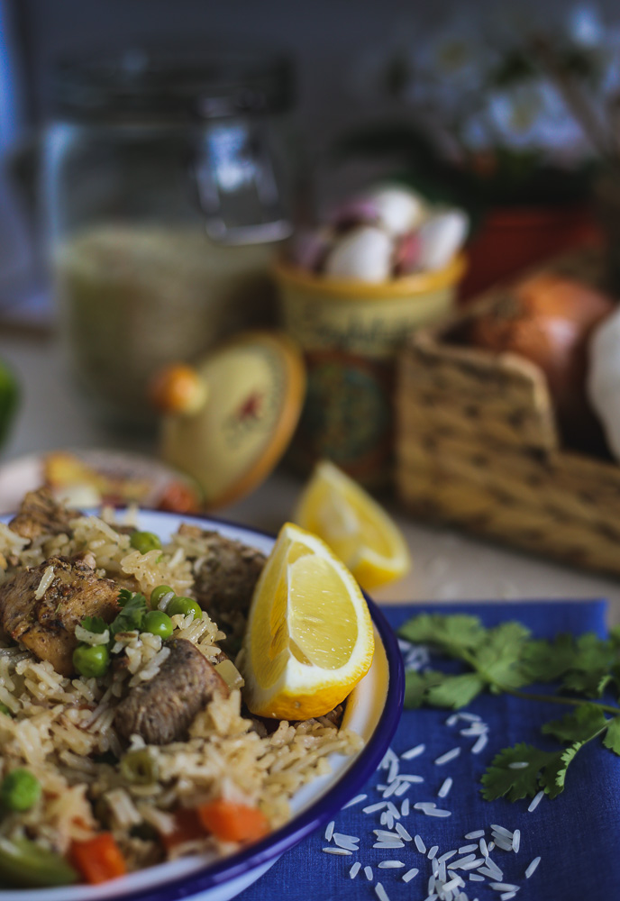 rice and chicken with a lemon wedge on a plate