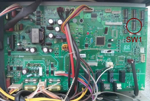 En la placa electrónica de la unidad exterior, habrá que localizar el elemento SW1 como se muestra en la imagen.