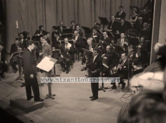 Ο Μπιθικώτσης λίγο προν καταρρεύσει. Αριστερα Ο θεοδωράκης και πρώτος στην ορχήστρα ο Μανώλης Χιώτη;ς. Ο Χατσιδάκις κάθεται εκτός πλάνου στο πιάνο.