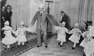 """Ο """"πατερούλης"""" Χότζα με παιδιά τα οποία φορούν παραδοσιακές στολές."""