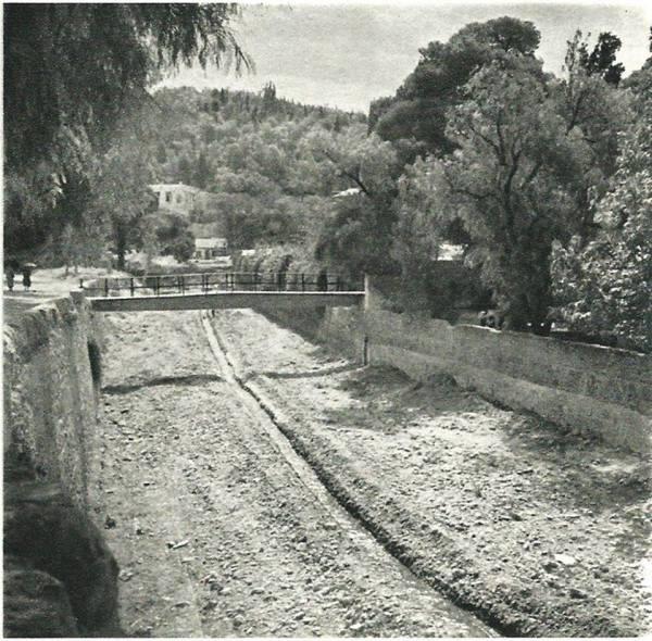 Αθήνα 1940. Η κοίτη του Ιλισσού με το γεφυράκι που πήγαινε κάποτε στο παριλίσιο θέατρο ΠΑΡΑΔΕΙΣΟΣ.Στο βάθος, ο λόφος του Αρδηττού και το σπίτι του Κωνσταντίνου Μαζαράκη - Αινιάν.