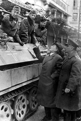 Heinrich Hoffmann, 9 Απριλίου 1941, Θεσσαλονίκη, Πλατεία Βαρδαρίου, ο Δήμαρχος Κώστας Μερκουρίου και ο στρατιωτικός διοικητής Αντιστράτηγος Νικόλαος Ραγκαβής, σπεύδουν να παραδώσουν τα κλειδιά της πόλης στον γερμανό στρατηγό.