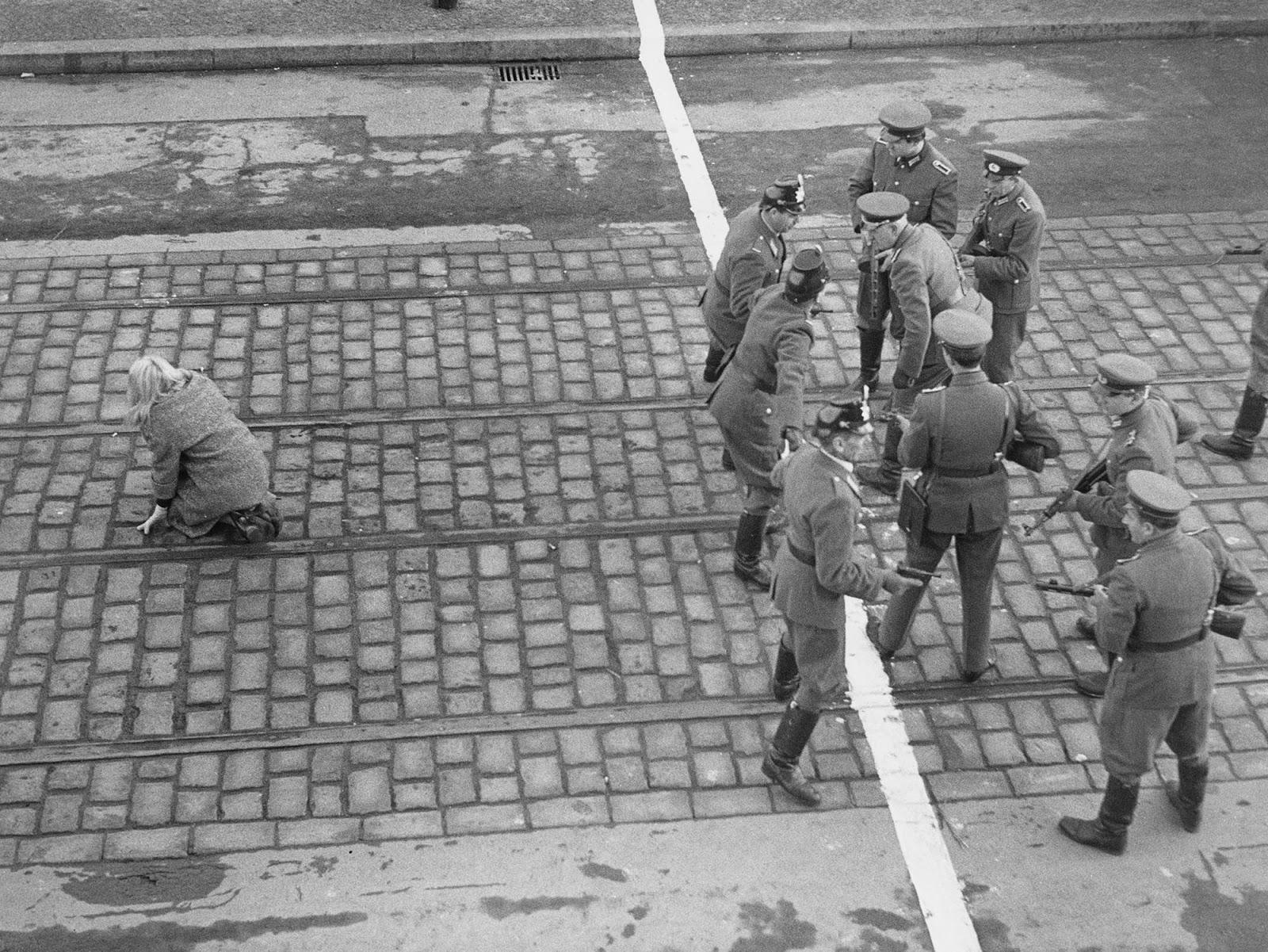 Μια γυναίκα έχει περάσει από το Ανατολικό στο Δυτικό Βερολίνο και ξεσπά διαμάχη μεταξύ των αστυνομικών. Πώς ένας κάτοικος της ανατολικής πλευράς μπορούσε να επισκεφθεί την άλλη. Τι μαρτυρούν τα όπλα και οι στολές τους