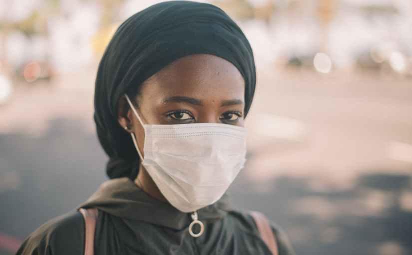 black female in medical mask on street