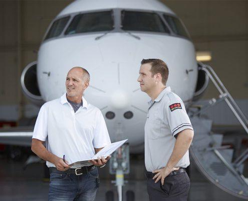 Security guard and pilot reviewing security at airport hangar