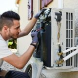 tech fixing air conditioner