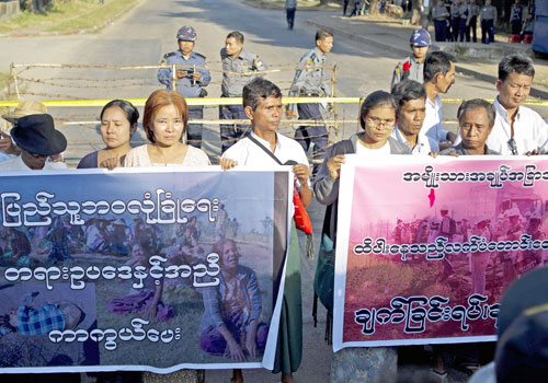 Protesters display banners in front of the Chinese embassy in Yangon on December 25, 2014. Photo: AFP