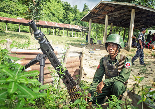 "A Tatmadaw soldier stands guard at an outpost in Maungdaw township, northern Rakhine State, after the area was declared an ""operation zone"" following a deadly attack on Border Guard Police on October 9. Photo: Kaung Htet / The Myanmar Times"