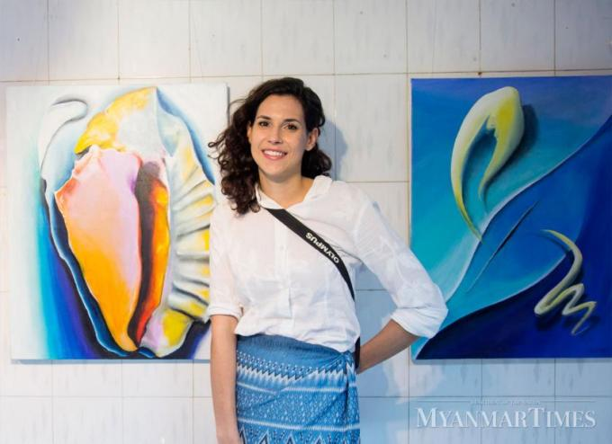 Melinda Dovak poses with her paintings. Nyan Zay Htet/The Myanmar Times