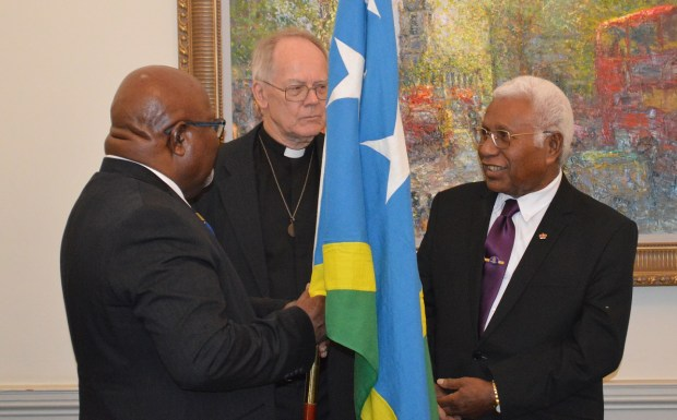 Canon John Pinder handing over the Solomon Islands flag to Sir David
