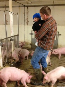 Grandpa showing grandson the pigs