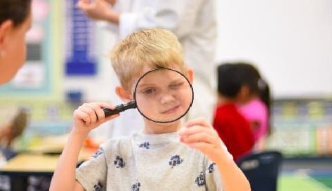Child Looking Through Magnifying Glass.
