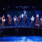 Cast of Newsies Holding Up Papers