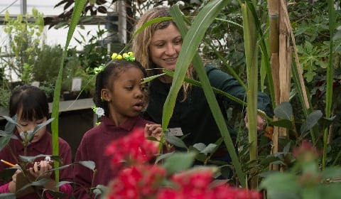 Teacher and student looking at plants