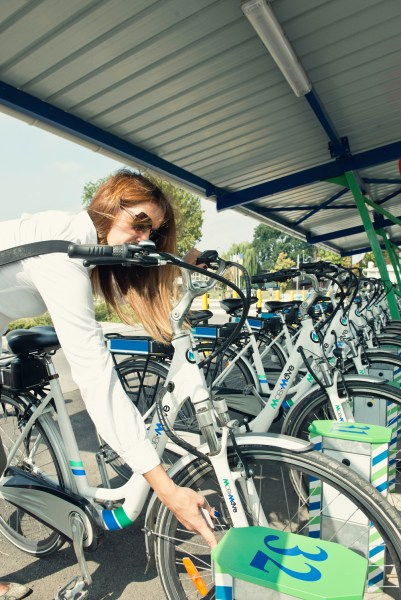 Young female commuter taking e-bike from bicycle sharing station